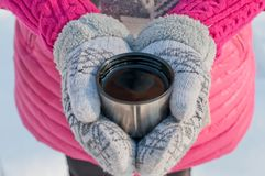 Hands in mittens hold a cup from a thermos with tea stock image