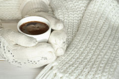 Hands in mittens holding cup of coffee Stock Photos