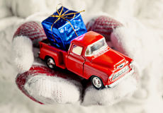 Hands in mittens holding a toy red vintage car with gift blue bo Stock Images