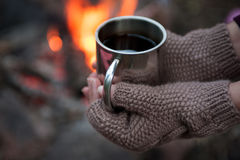 Hands in mitts holding hot tea cup outdoor near bonfire Stock Photos