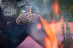 Hands in mitts holding hot tea cup outdoor near bonfire Stock Image