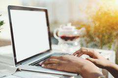 Hands of mixed woman on keyboard of laptop. View of accurate black female hands working with laptop in cafe on sunny springtime, arms of biracial woman on Royalty Free Stock Images