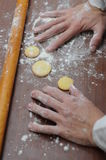Hands mixing fluor with cookies. Baked cookies at workplace and rolling pin and hands that touching flour Royalty Free Stock Photography