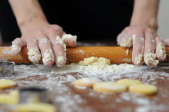 Hands mixing fluor with cookies. Baked cookies at workplace and rolling pin and hands that touching flour Stock Photos