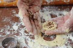 Hands mixing fluor with cookies. Baked cookies at workplace and rolling pin and hands that touching flour Stock Image