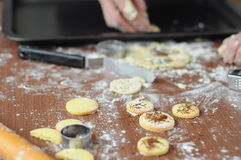 Hands mixing fluor with cookies. Baked cookies at workplace and rolling pin and hands that touching flour Stock Images