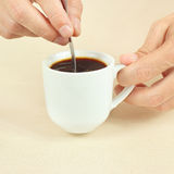 Hands mixing with spoon of black coffee in the cup Royalty Free Stock Images