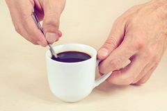 Hands mixing with spoon of hot coffee in the cup, gently toned Stock Image