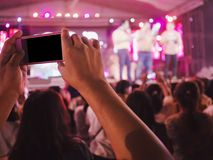 Hands with mobile smart phone recording and taking a picture at music concert.  royalty free stock photography