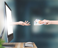 Hands with money come out of pc monitor Royalty Free Stock Photos
