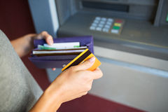 Hands with money and credit card at atm machine Stock Image