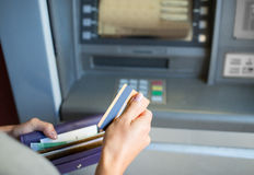Hands with money and credit card at atm machine Royalty Free Stock Image