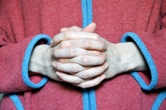 The hands of a monk, folded in a prayer posture Stock Photo