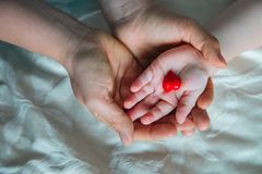 Hands of mother and baby holding heart. Love and family concept royalty free stock photography