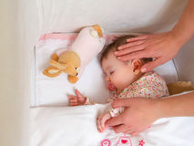 Hands of mother caressing her baby girl sleeping Stock Photography
