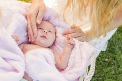 Hands of Mother Caressing Her Newborn Baby Girl. Gentle Hands of Mother Caressing Her Newborn Baby Girl in Pink Blanket Stock Photography