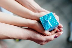 Hands of mother and child holding little box Stock Photos