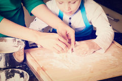 Hands of mother and child kneading dough Stock Photography