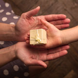 Hands of mother and child receiving gifts. Top view close up of mother and child hands holding a small yellow gift box in palm stock images