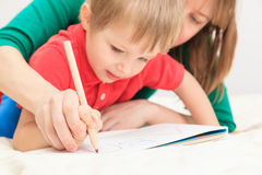 Hands of mother and child writing letters. Early education Stock Photos