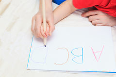 Hands of mother and child writing letters. Early education Royalty Free Stock Photography