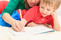 Hands of mother and child writing letters. Early education Stock Image