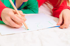 Hands of mother and child writing numbers. Early education Royalty Free Stock Image
