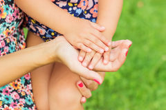 Hands of mother and daughter holding each other. Summer park in background Royalty Free Stock Photography