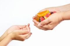 Hands of mother give colorful sweets and jelly in hands child Royalty Free Stock Photos