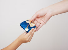 Hands of mother gives the purse to her little daughter Royalty Free Stock Photo