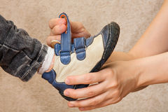 Hands of mother helping her child to put shoes Stock Photos