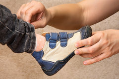 Hands of mother put on shoes child Stock Photos