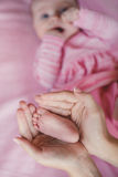 Hands of mother tenderly holding a tiny baby's legs. Royalty Free Stock Image