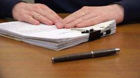 Hands move a stack of documents to the pen on the table