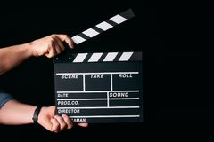 Hands with a movie clapperboard. Isolated on black background with copy space, close-up. Wooden clapper board as cinema and movie time concept Stock Photography