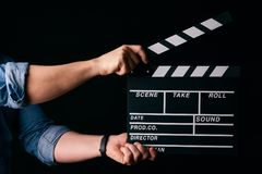 Hands with a movie clapperboard. A movie production clapper board. Hands with a movie clapperboard on black background with copy space, close-up Royalty Free Stock Image