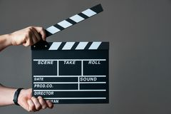 Hands with a movie clapperboard. A movie production clapper board. Hands with a movie clapperboard on grey background with copy space, close-up Stock Photography