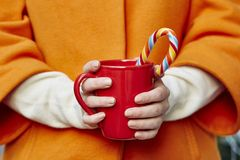 Hands with mug and candy Royalty Free Stock Photography