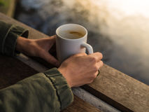 Hands with mug by water Royalty Free Stock Photos