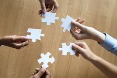 Hands of multiethnic associate partners employees holding puzzle pieces. Hands of multi ethnic associate partners employees team holding puzzle pieces finding royalty free stock photography