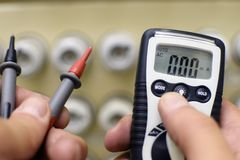 Hands with multimeter in front of the old fuse box. Space for text royalty free stock photo
