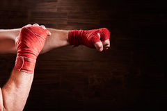 Hands of muscular athletic man with red bandage against brown background. Stock Image