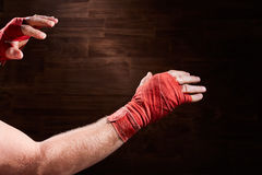Hands of muscular athletic man with red bandage against brown background. Royalty Free Stock Photography