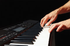 Hands of musician play the keys of the electronic synth on black background Royalty Free Stock Images