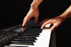 Hands of musician play the keys of the synthesizer on black background Royalty Free Stock Image