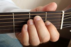 Hands of a musician playing classical acoustic guitar. Close-up. Chord Stock Photography