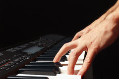 Hands of musician playing the electronic synth on black background Stock Photo