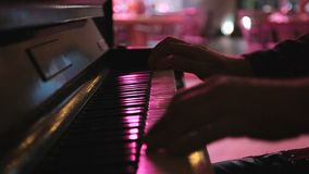 Hands of musician playing keyboard in concert in night club stock video footage