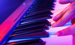 Hands of musician playing keyboard in concert with shallow depth Royalty Free Stock Images