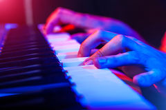 Hands of musician playing keyboard in concert with shallow depth Royalty Free Stock Image